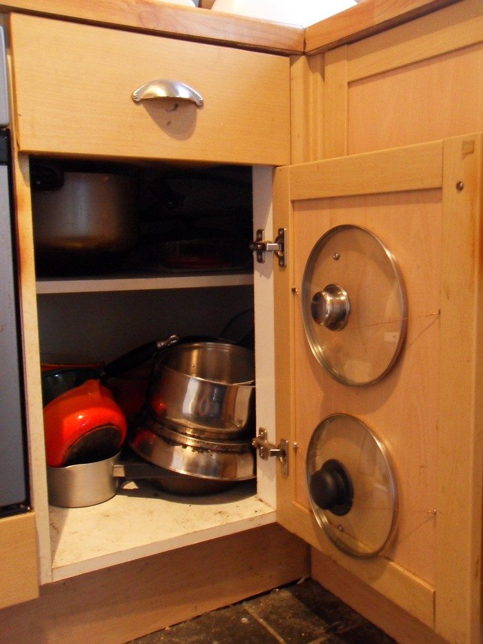 Reclaim never-used space (like the walls of a cupboard) with vertical storage. You can purchase a dedicated pot lid rack that operates like this, but a magazine rack is another clever stand-in.